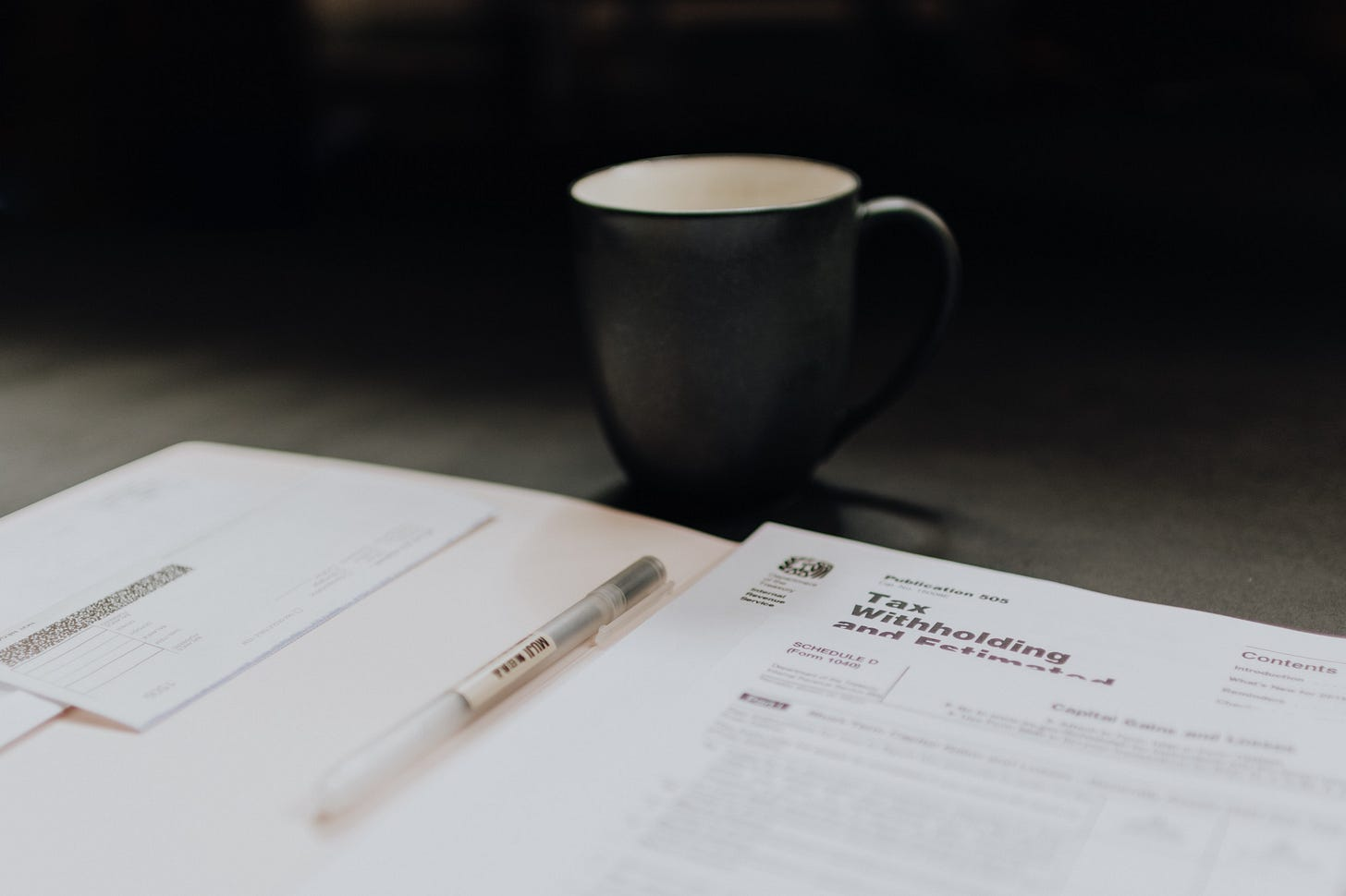 image of a cup of coffee beside tax forms for article by larry g maguire