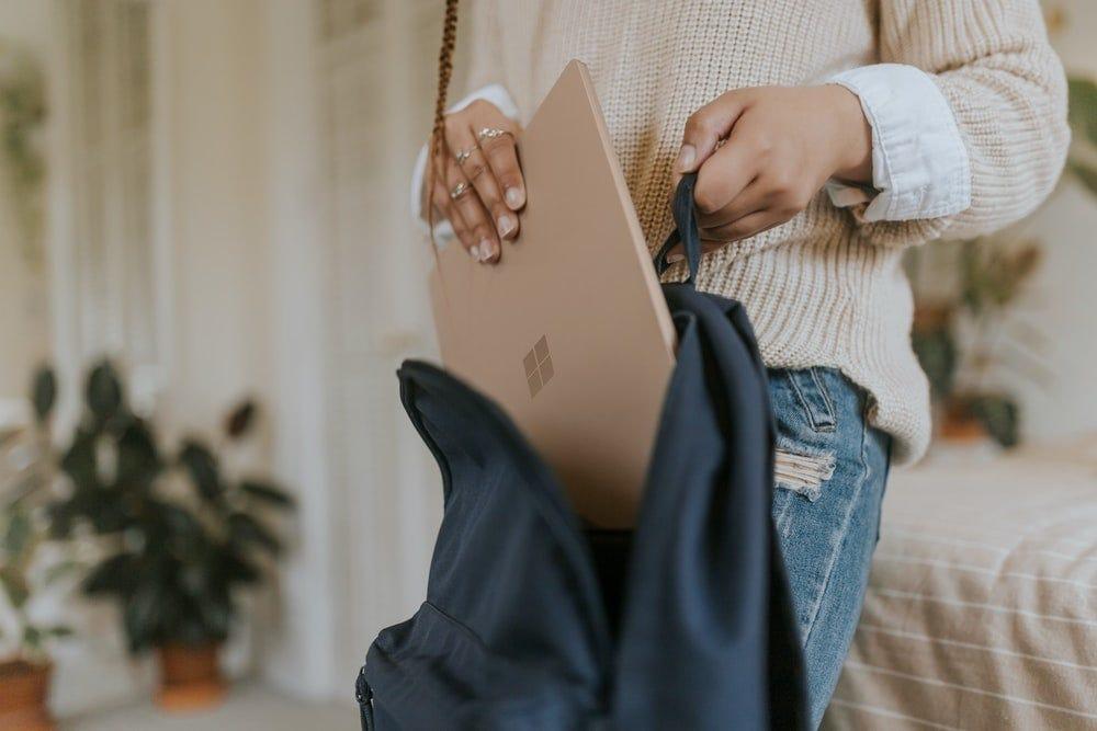 woman in blue denim jeans holding sandstone surface laptop