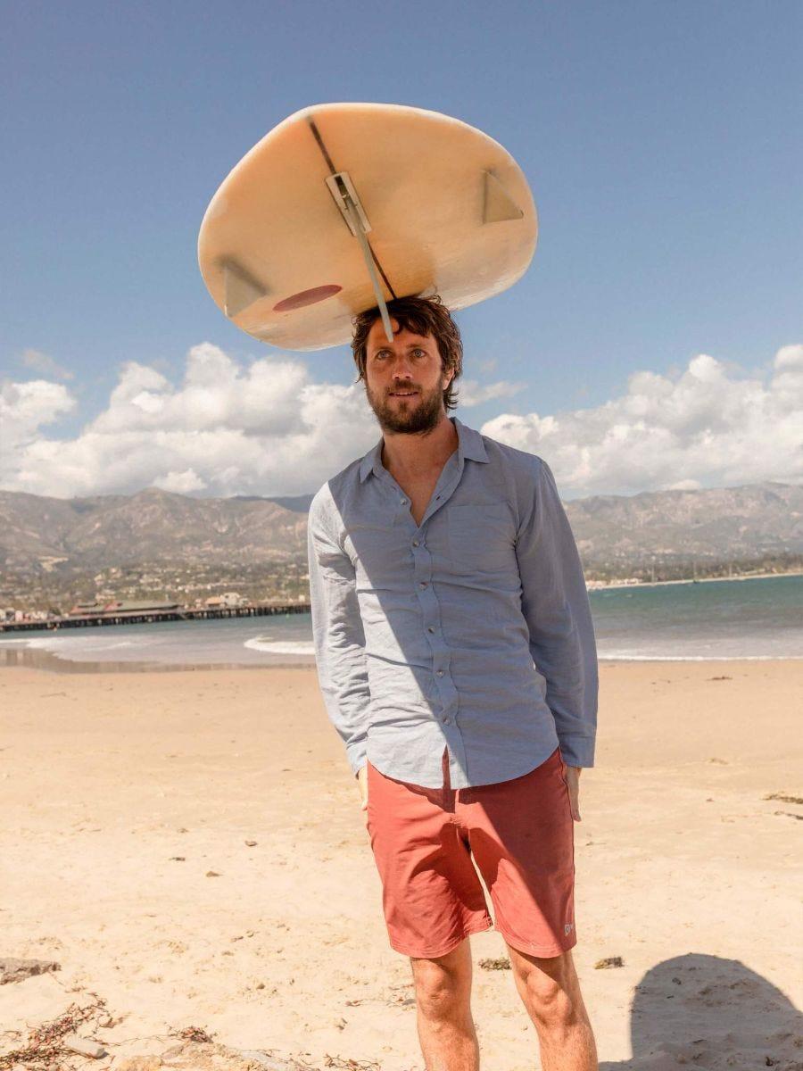 a man balances a surfboard on his head while wearing a blue linen shirt on a beach