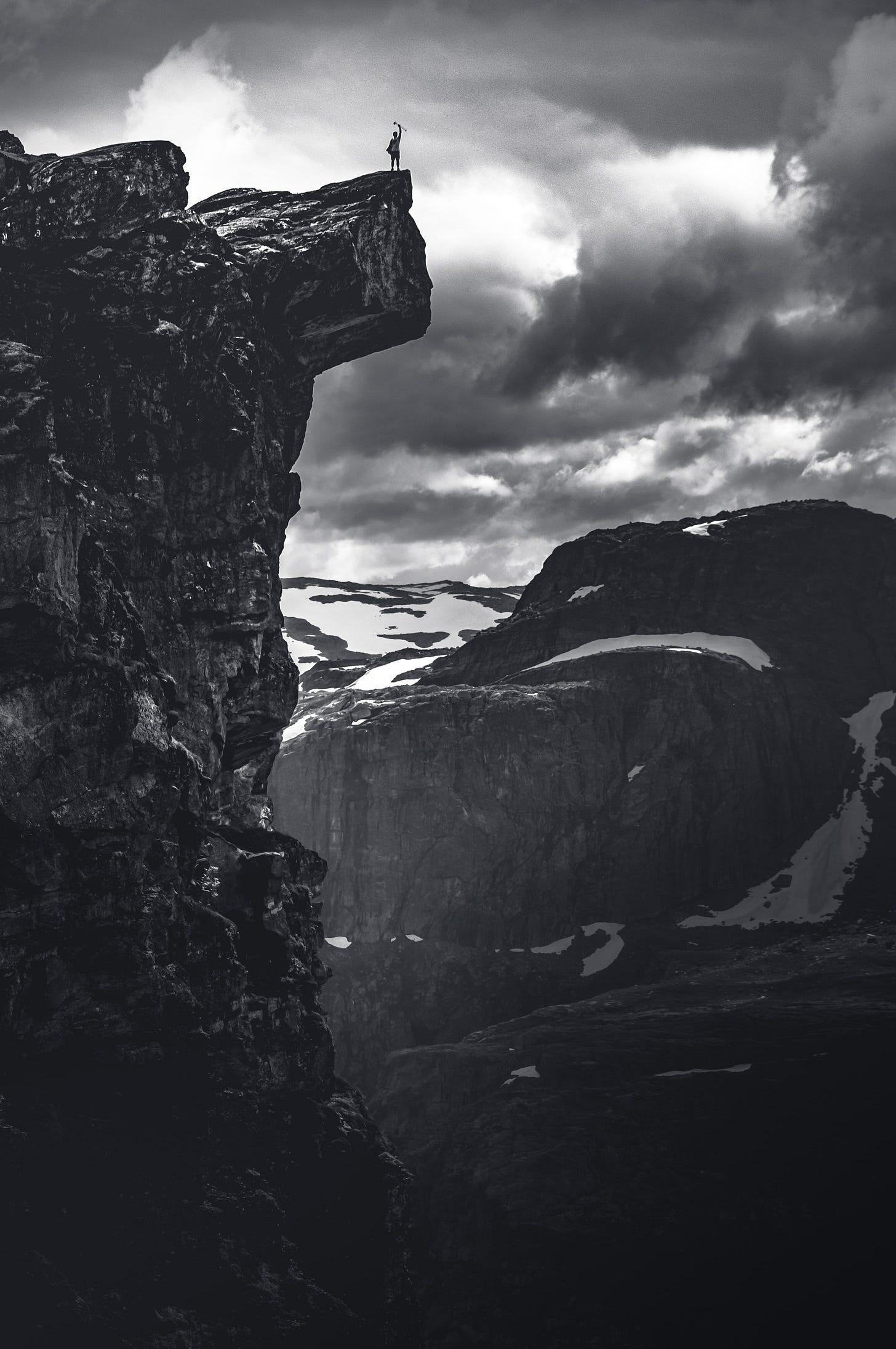 imagem em preto e branco de uma paisagem com um abismo e montanhas ao fundo