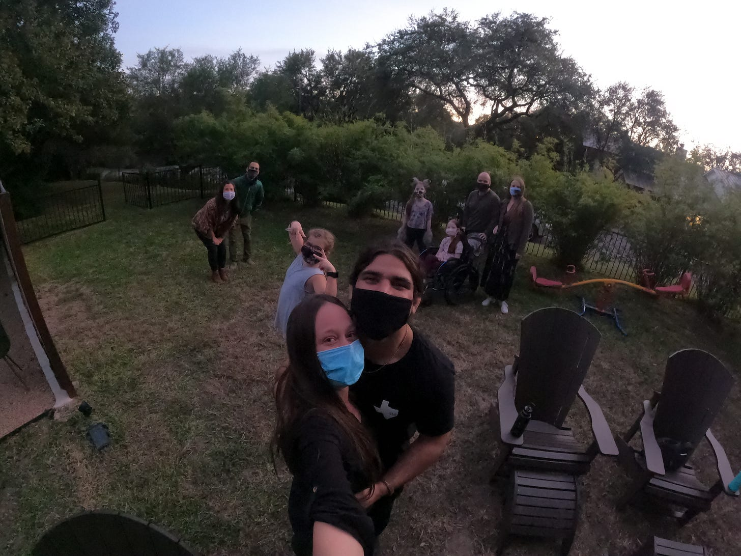Anthony and Kelly stand and selfie with the backyard audience everyone is wearing masks!