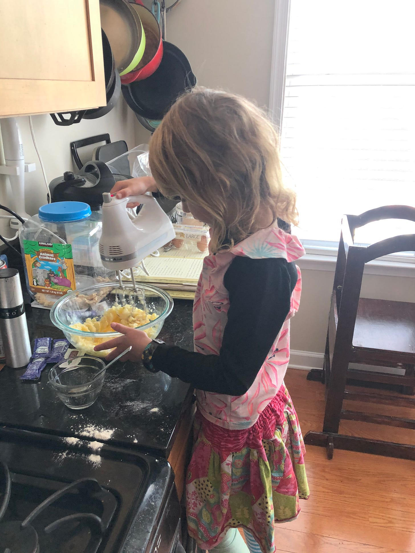 Molly stands at a counter with a mixer and a mixing bowl.