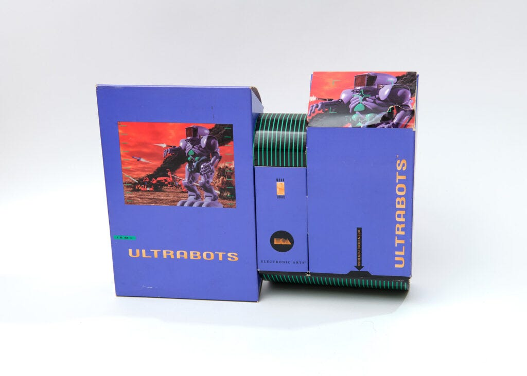 The box for Ultrabots. It consists of three differently-sized rectangular purple boxes stacked next to each other. The boxes are decorated with a combination of game art, featuring a large purple robot, and black-and-green cybernetic stripe patterns.