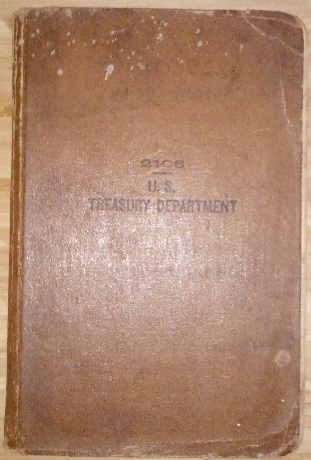 """Photograph of a brown book with the words """"2106 – U.S. Treasury Department"""" printed on it in black"""