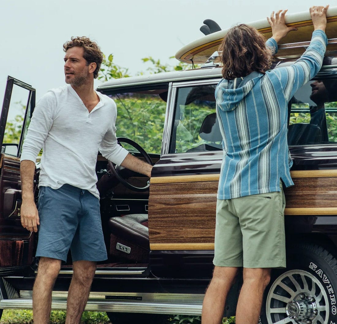 two men wearing faherty all day shorts load surfboards up on a car