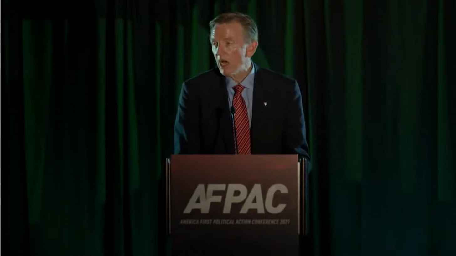 Paul Gosar is seen standing behind a lectern with the letters AFPAC on the front. He is standing in front of a dark green curtain. He is wearing a suit and tie, and his face is shiny with sweat.