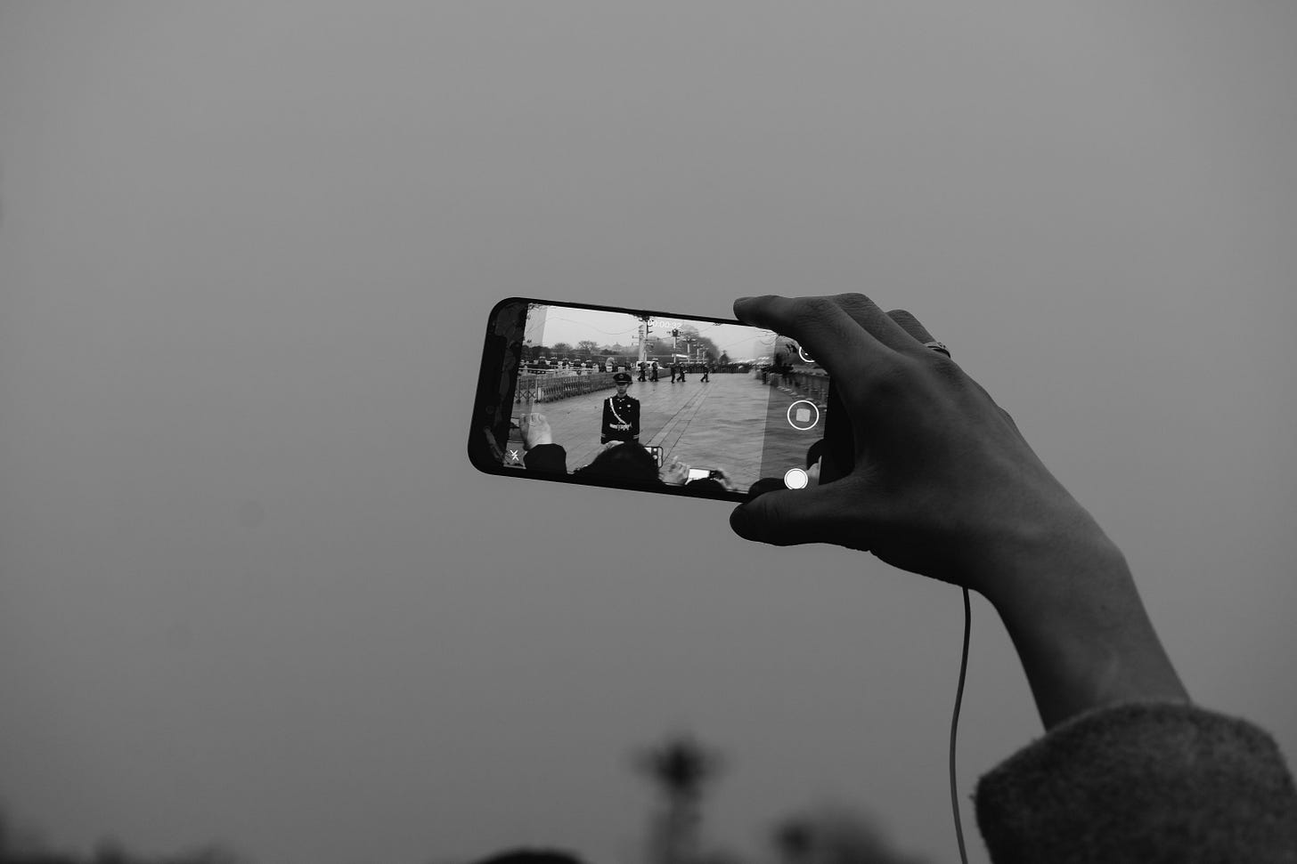 Grayscale photo of a hand holding an iphone taking video. Markus Winkler / Unsplash