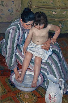 A mother dressed in a striped dress with long sleeves and turtleneck helps her small daughter wash her feet. She wears her shiny black hair in a loose bun and holds the child securely. The girl is sitting in her mother's lap and her waist is wrapped in a white towel. She watches as her mother gently dips her small legs into the purple-rimmed glass bowl that stirs below with water. In the right-hand corner, a white water pitcher with different shades of pink flowers is standing on the orange-patterned carpet. In the background a yellow wardrobe with tiny flowers and golden handles sits against the flowery wallpaper.