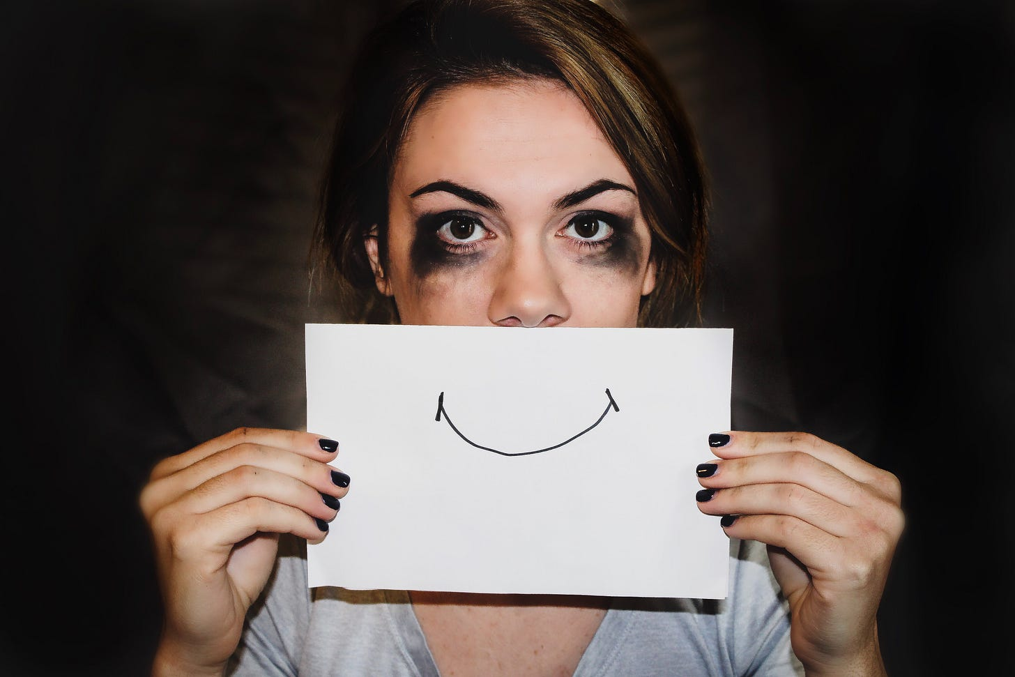 Photo of a woman with black eye makeup holding up a paper with a smiling face over her mouth. Sydney Sims / Unsplash