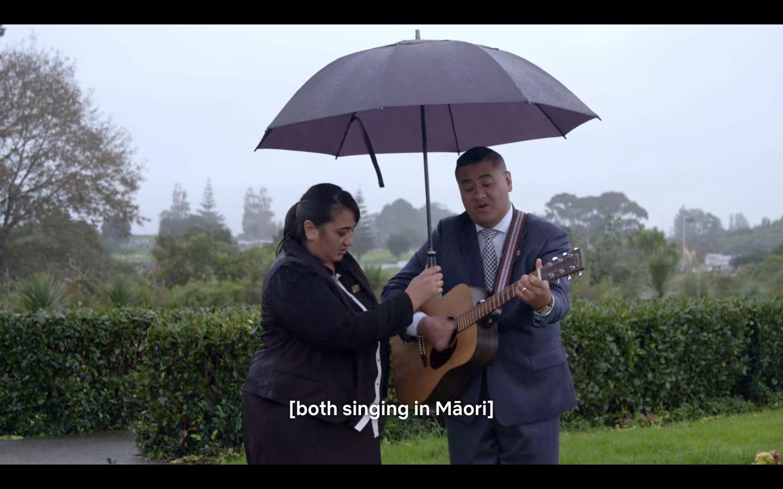 """L'homme et la femme chantent et jouent de la guitare sous la pluie, les sous-titres disent """"both singing in Maori"""""""