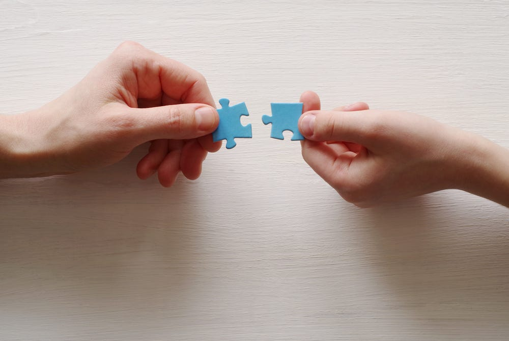 Puzzles. Hand of the child and hand of mother fold puzzle, closeup, top view