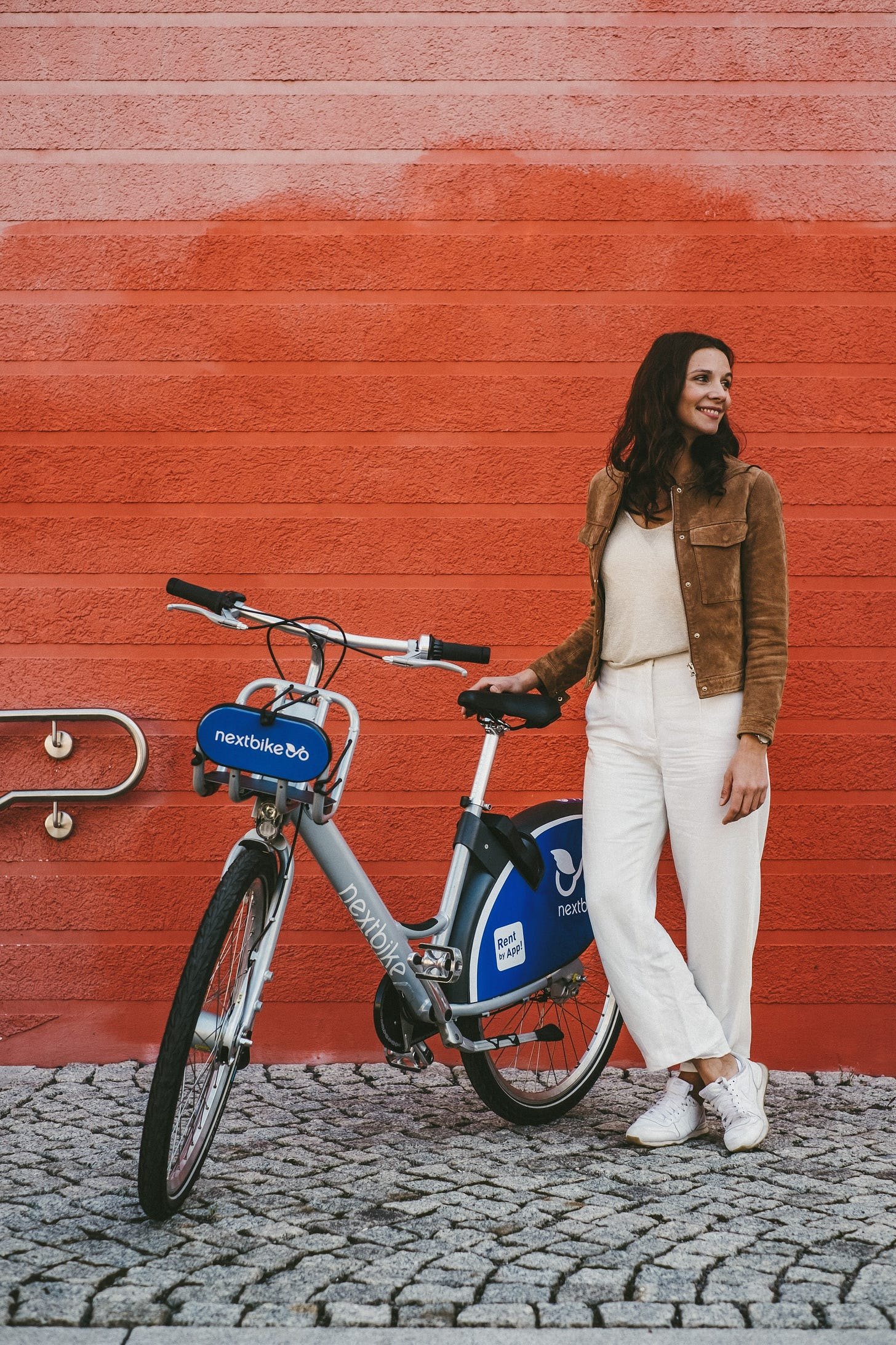 Woman standing next to a bike from a bike-sharing company
