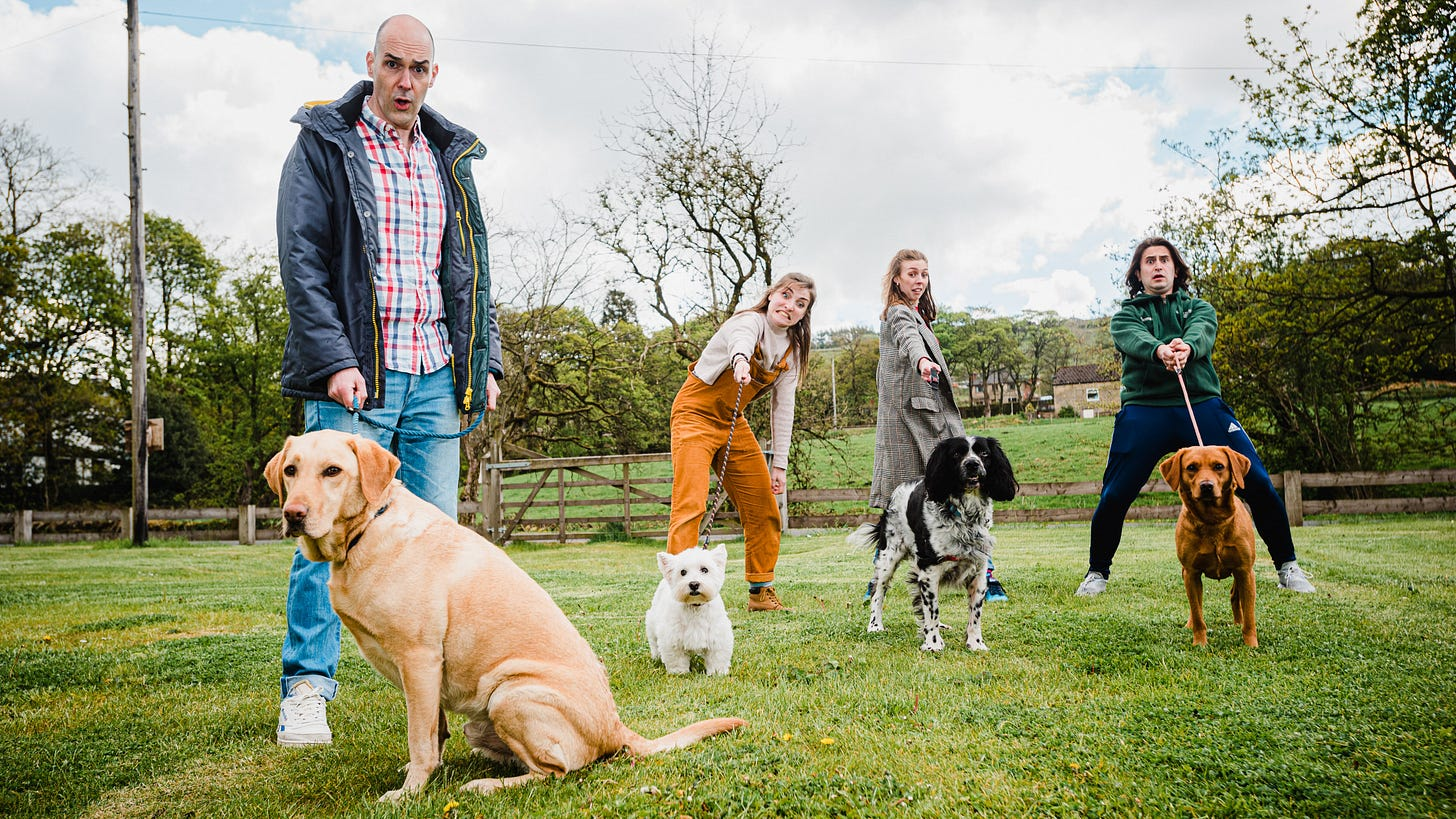James Mclean, Rachel Benson, Elizabeth Robin and Thomas Cotran with dogs in a field.
