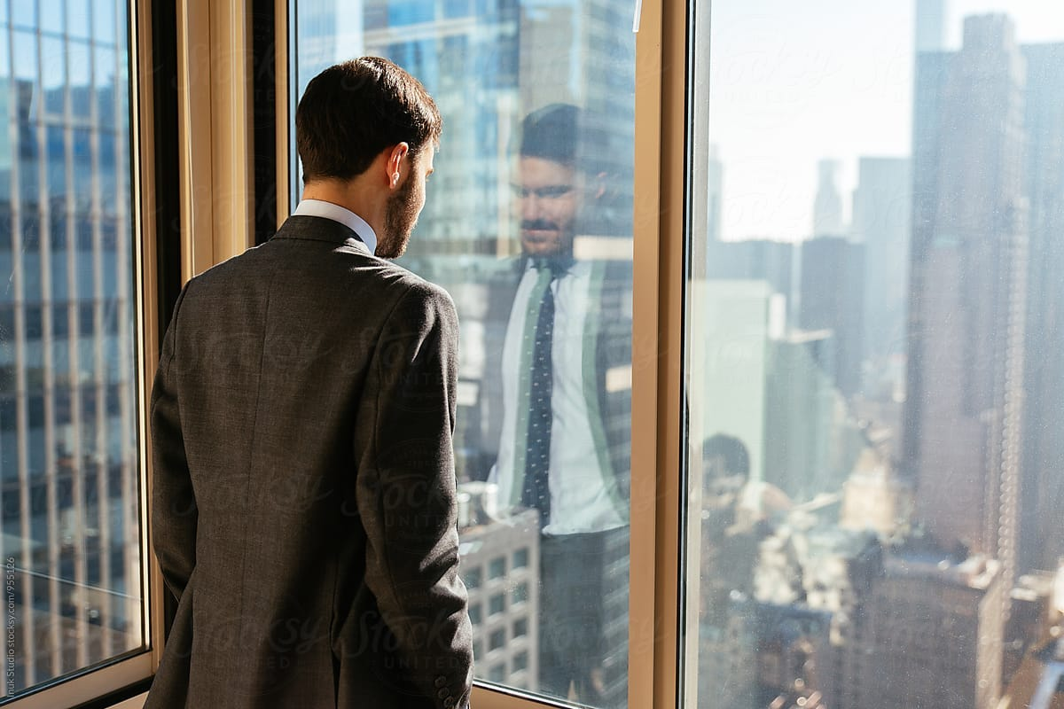 Businessman looking through window at city from the office by Inuk Studio -  Stocksy United