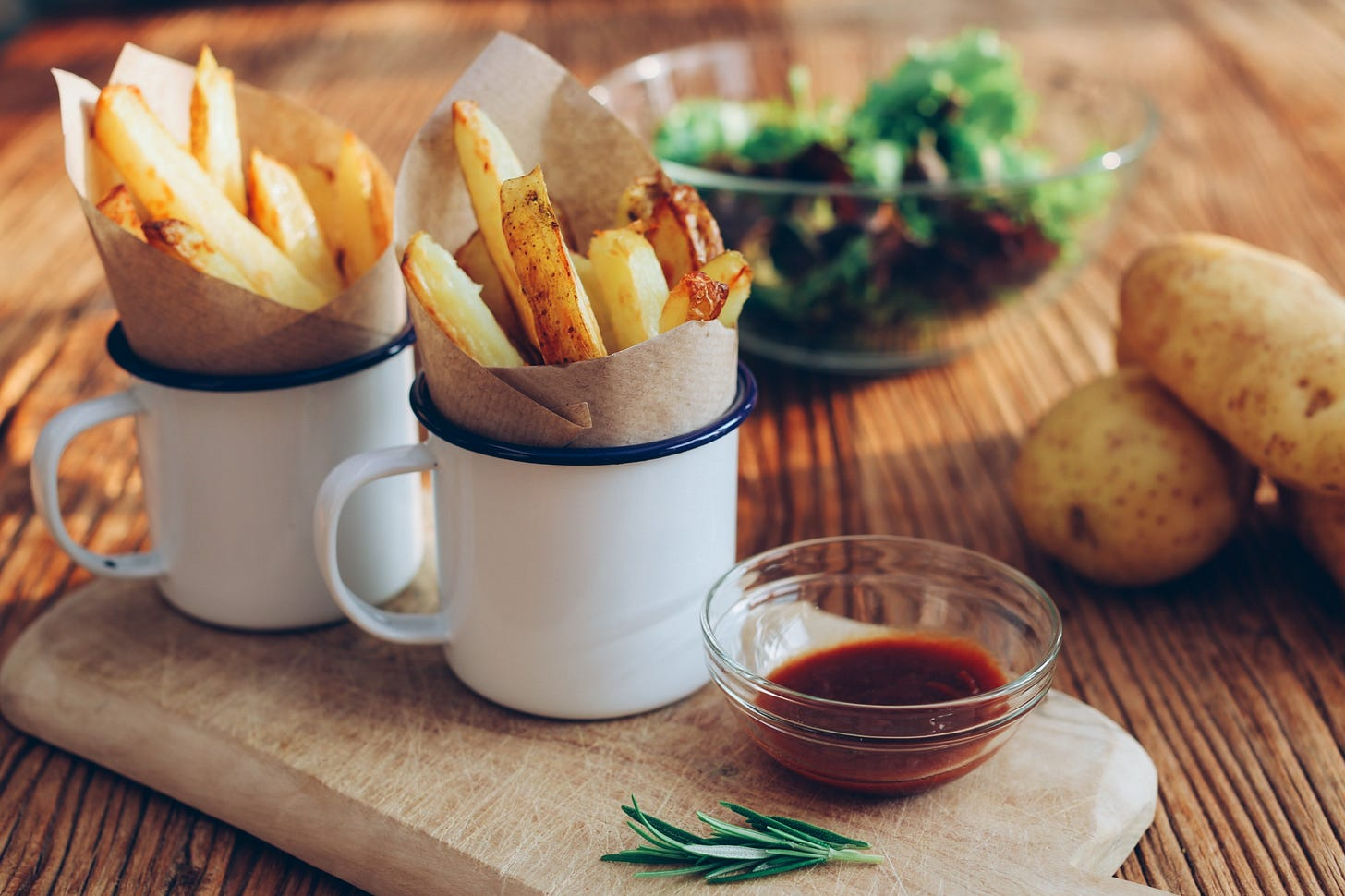 Two cups filled with French fries.
