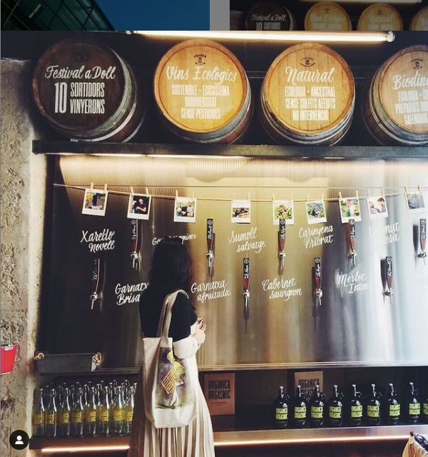Girl standing in front of natural wine barrels and taps to fill wine to-go
