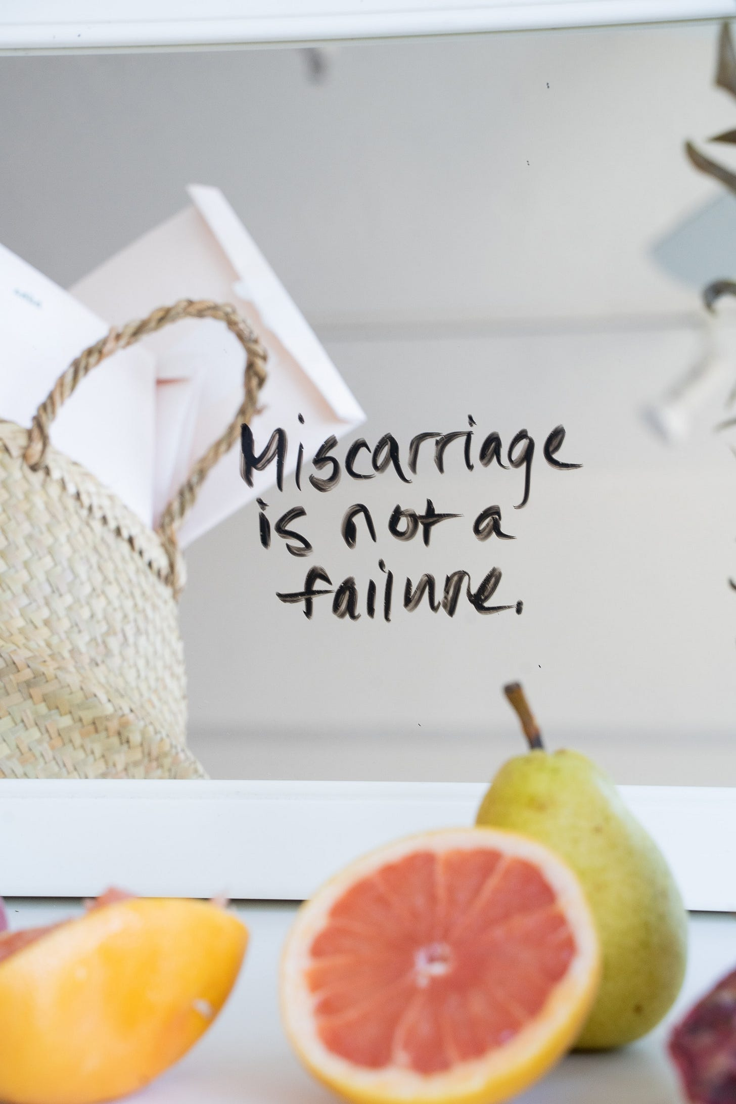 """half grapefruit and a pear on a counter top with the words """"Miscarriage is not a failure"""" written over top"""