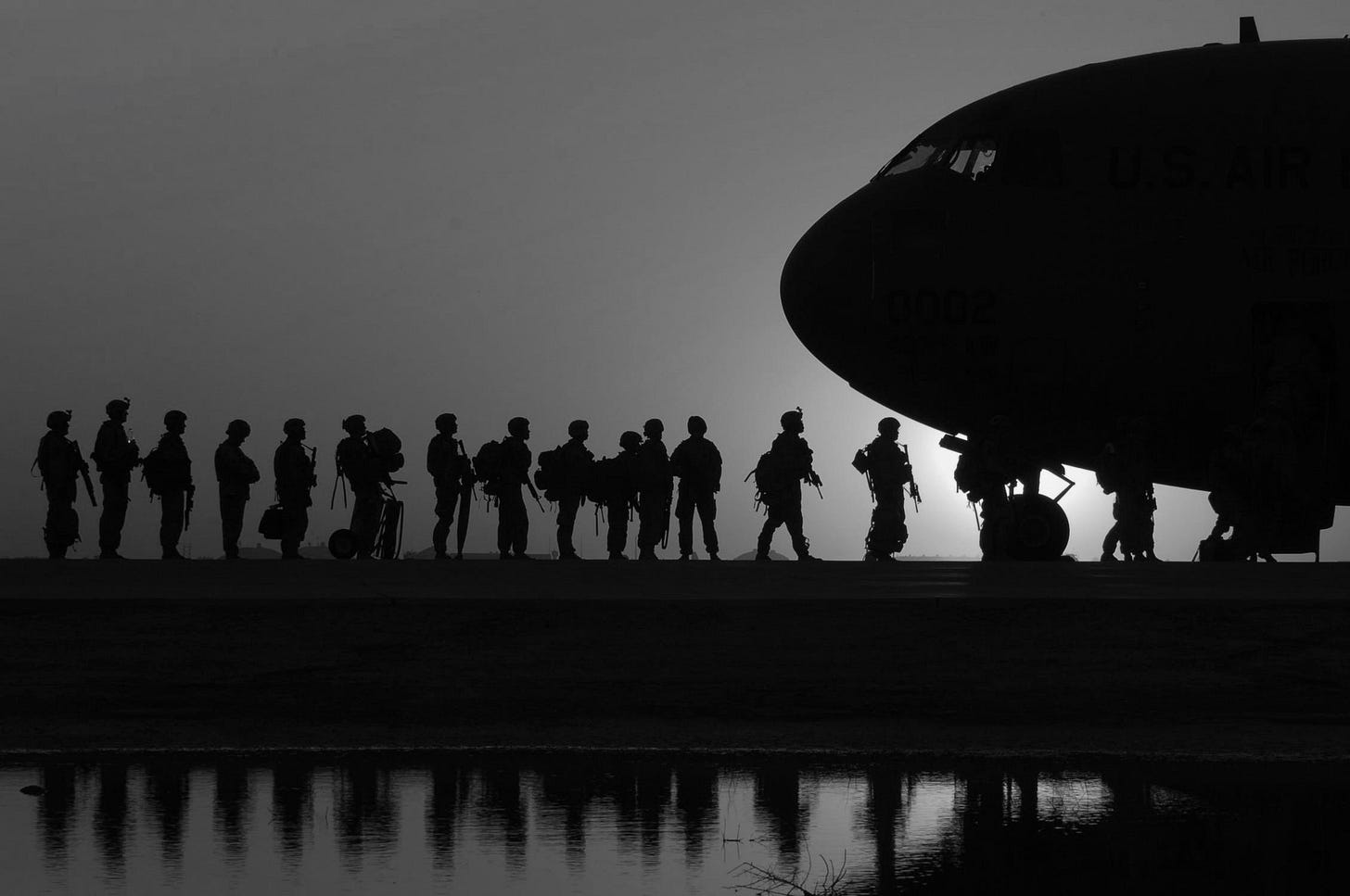 At dusk or dawn, the silhouettes of soldiers lined up to board a jet
