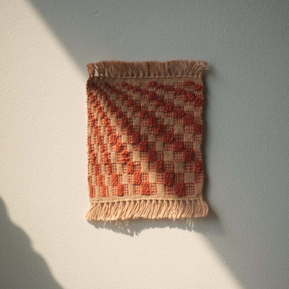 A small woven sample with diagonal lines going from top left to bottom right