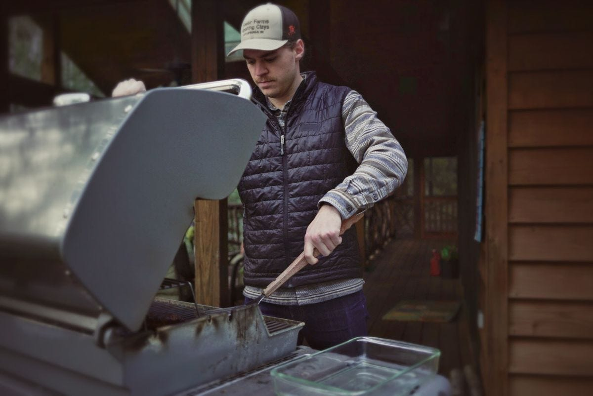 ryan wears a patagonia nano puff vest while grilling steaks