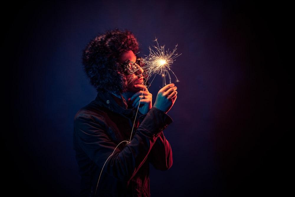 man in black jacket holding spark