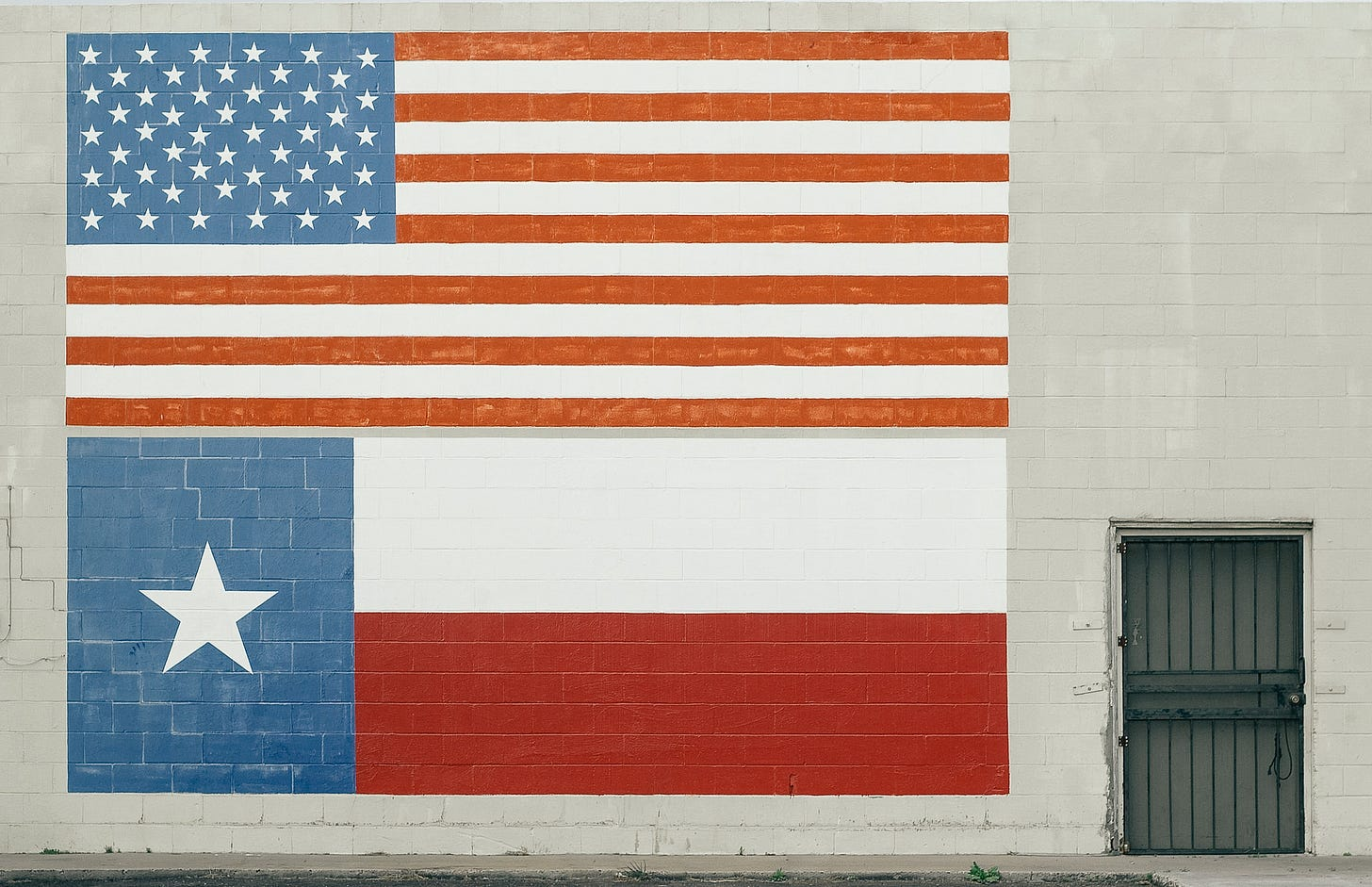 A mural of the American flag above a mural of the Texas flag, both pointed on the exterior of a white brick building. Matthew T. Rader / Unsplash