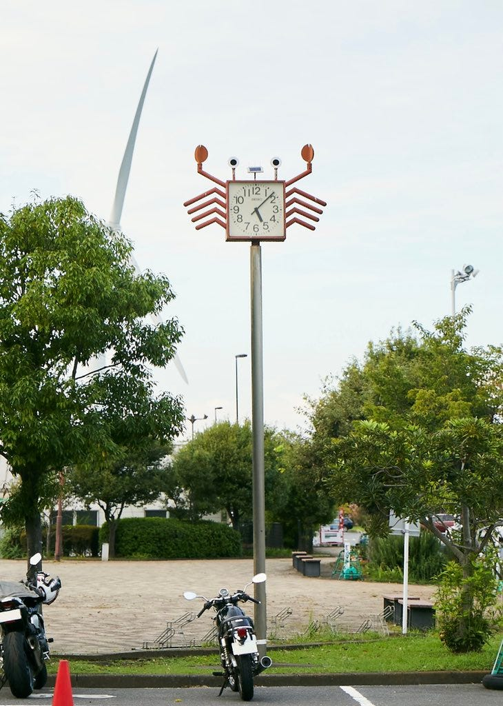 A clock on top of a tall pole that looks like an adorable lil crab guy.
