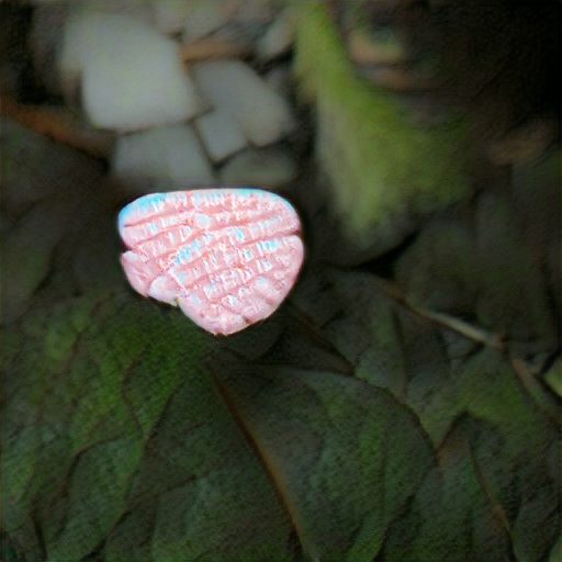 A pink candy on a leafy green background. There are several lines of closely-spaced illegible white text on the candy.