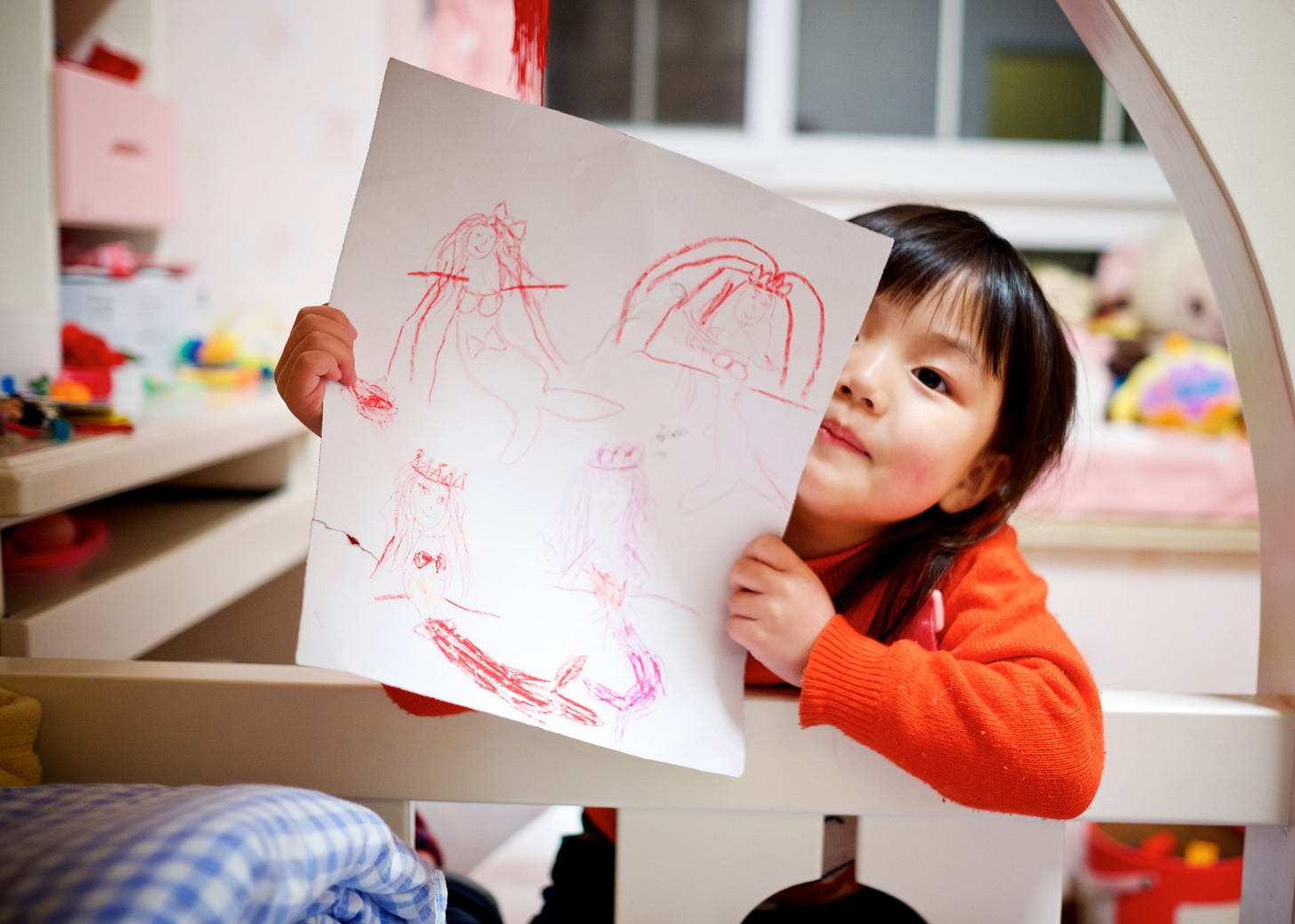 preschool asian girl holding up a crayon drawing of a mermaid