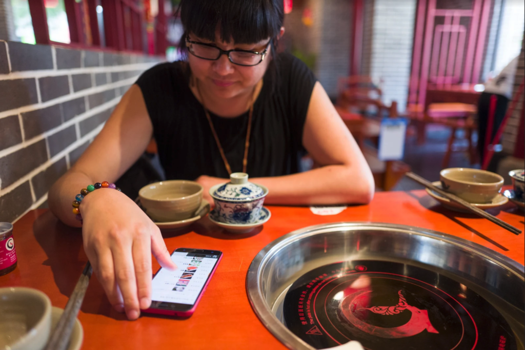 An Xiao Mina sitting at a hot pot table and scrolling through a phone