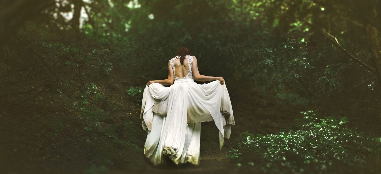 a woman in what is probably a white wedding dress walking into the forest