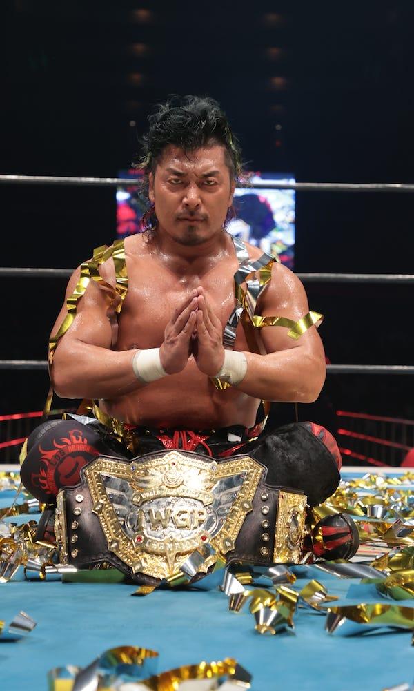 Shingo Takagi sits with the IWGP World title belt