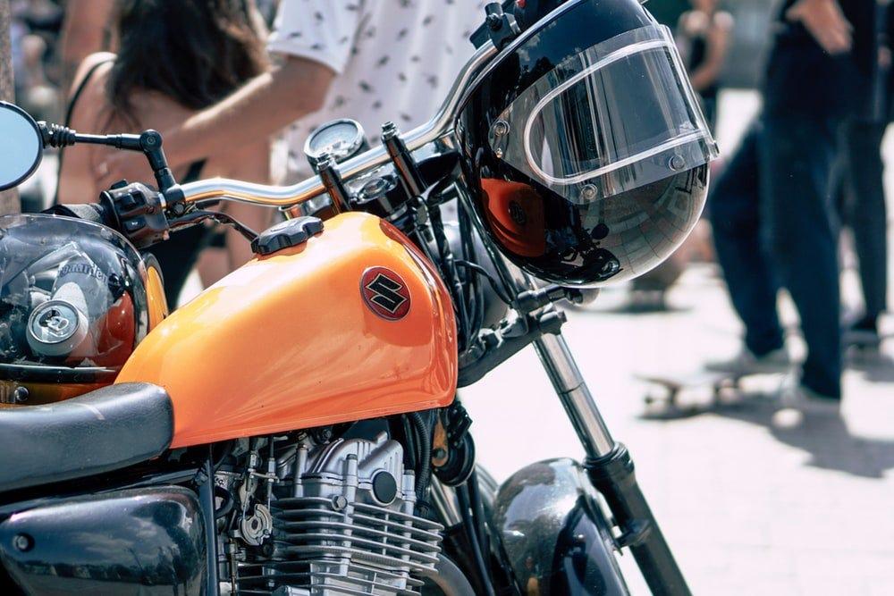 black helmet hanging on black and orange Suzuki motorcycle