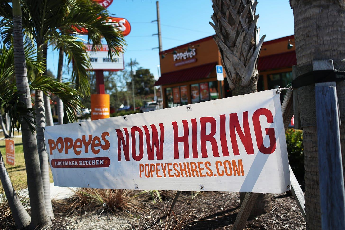 A 'Now Hiring' sign hangs in front of a Popeye's restaurant on February 04, 2021 in Miami, Florida