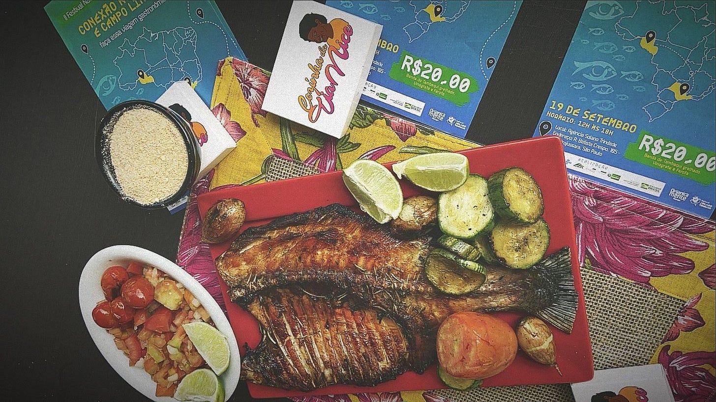 imagem mostra prato de peixe assado ao lado de travessa com farinha, acompanhado e fatias de limão