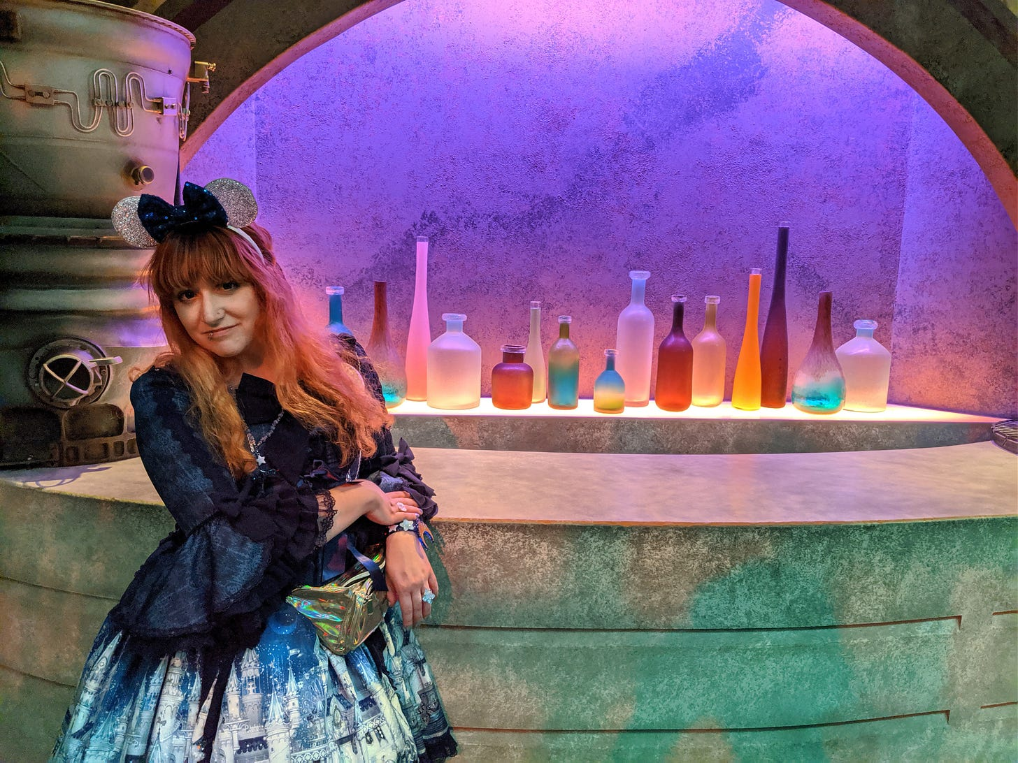 Photo taken in 2019 at Disneyland. Nif (a white femme with red/orange hair) is wearing glittery silver mouse ears with a navy sequined bow. She is wearing Angelic Pretty's Castle Mirage princess sleeve OP in navy, with a metallic gold fanny pack, and an assortment of AP acrylic jewelry. She is standing in front of a Star Wars bar display, with brightly-colored bottles behind the bar and industrial-styled tank on the bar top.