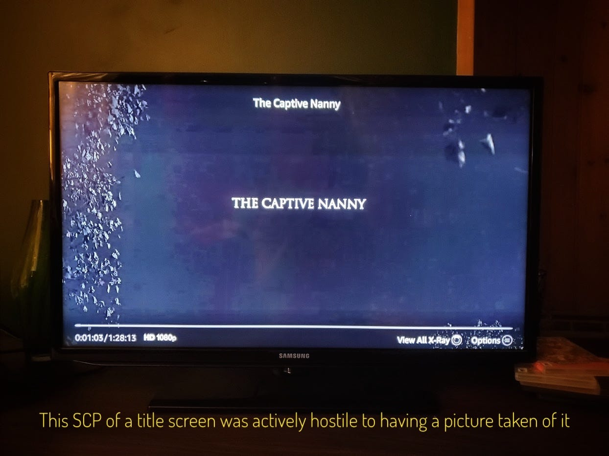 """A blurry black title screen with leaves on the side of the screen, captioned """"This SCP of a title screen was actively hostile to having a picture taken of it"""""""