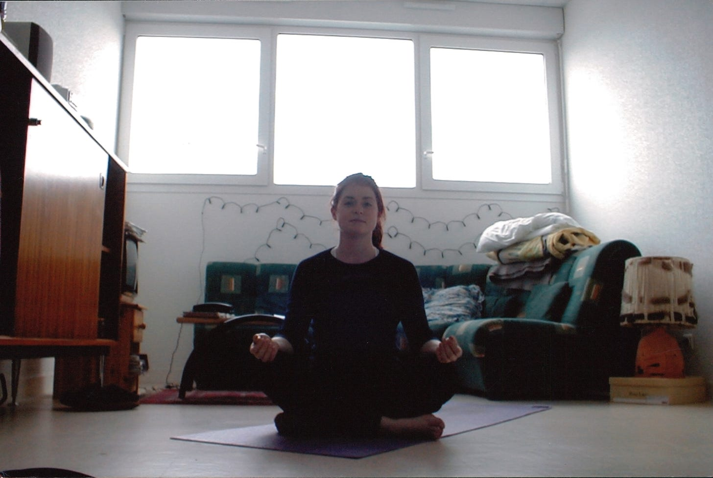 Charlotte sits in her apartment living room on a purple yoga mat with her legs folded and her wrists resting on her knees.