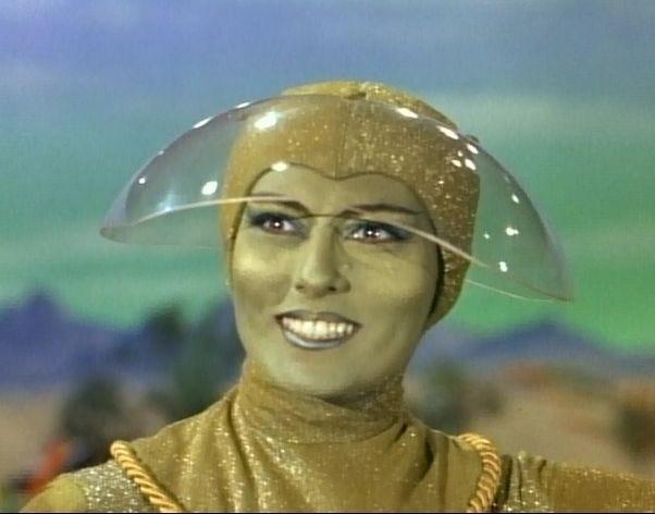 Foto de uma série antiga com uma mulher completamente verde, com roupa e touca verde brilhante e uma viseira de acrílico, sorrindo de forma bem esquisita