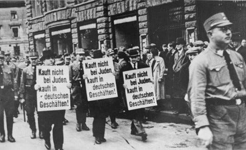 """<p>Three Jewish businessmen are forced to march down a crowded Leipzig street while carrying signs reading: """"Don't buy from Jews. Shop in German businesses!"""" Leipzig, Germany, 1935.</p>"""
