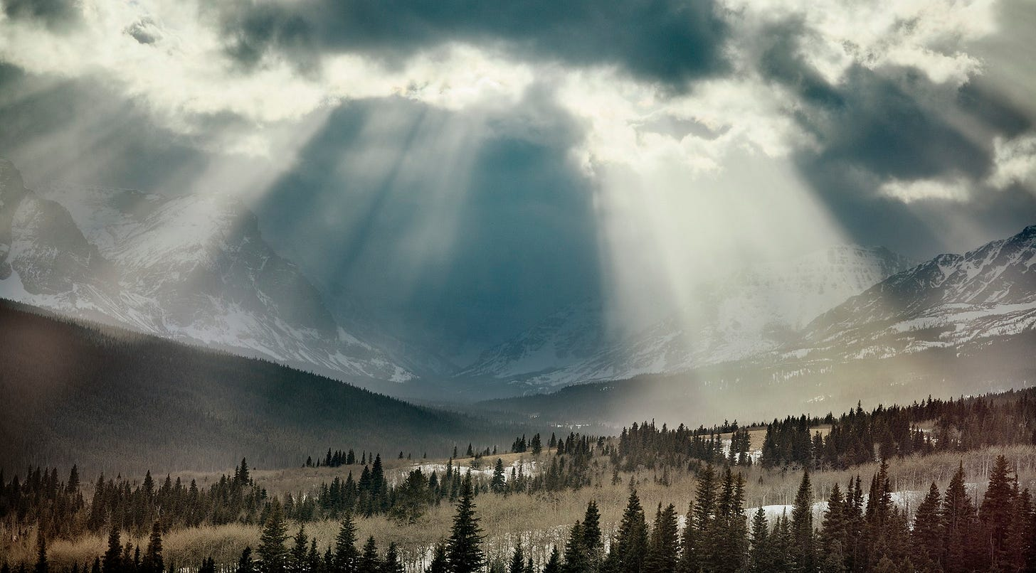 photo of Glacier National Park, Montana, with light streaming through clouds