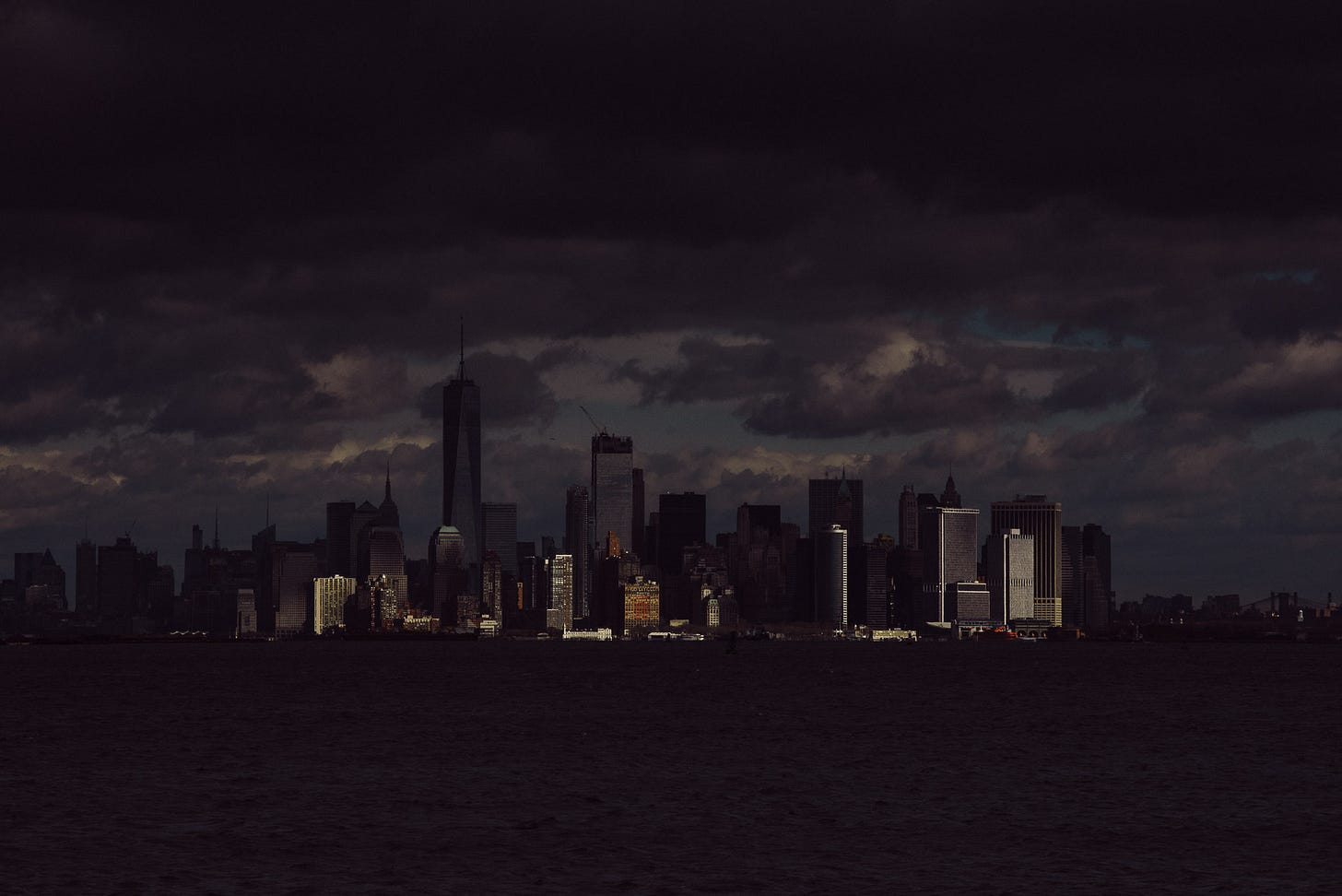 A dark and moody photo of the island of Manhattan. Just a few buildings are lit by sunshine.