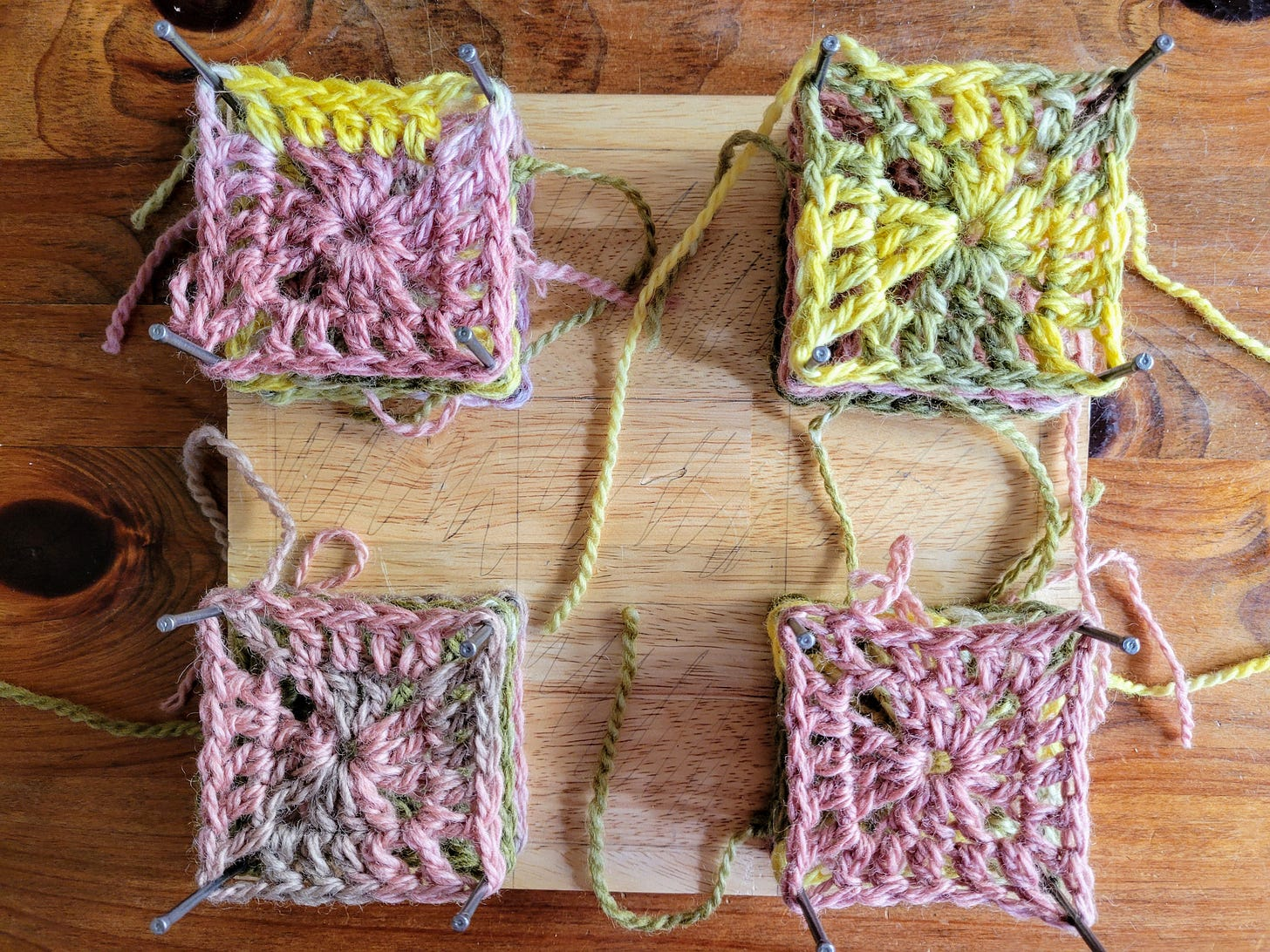Photo of granny squares blocking on a piece of wood.