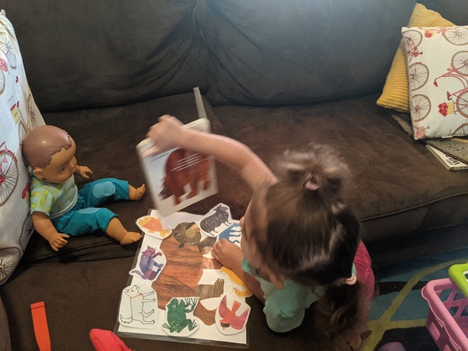 Image of Lila holding a board book up to a babydoll who is sitting on the couch.  A laminated set of animal photos on a paper is in front of her.