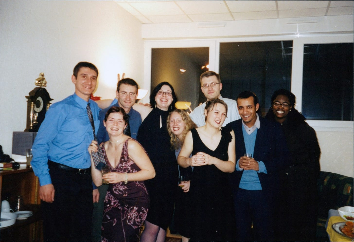 A group of men and women in festive dinner dress standing and smiling for the camera.