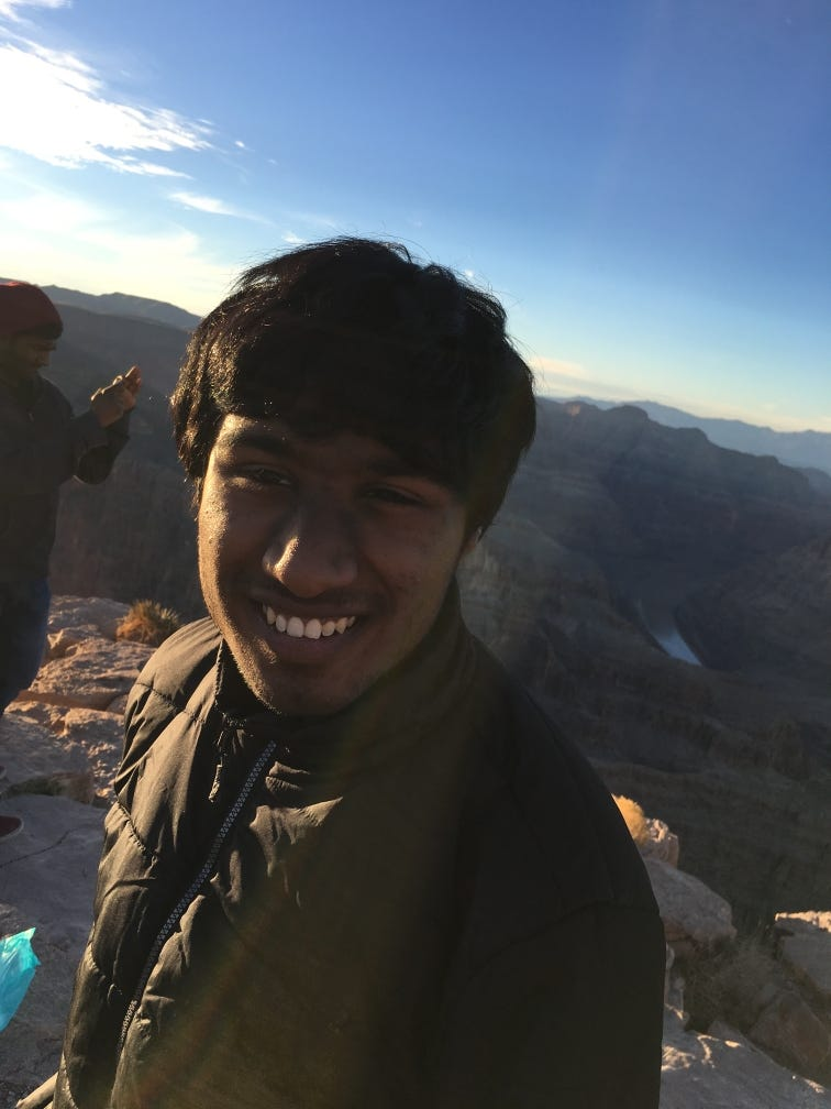 Kani Krishnan stands, smiling, in a dark green jacket before a breathtaking landscape of canyons.