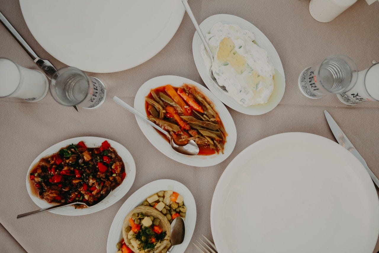 Photo of four food dishes and two empty plates on a table.
