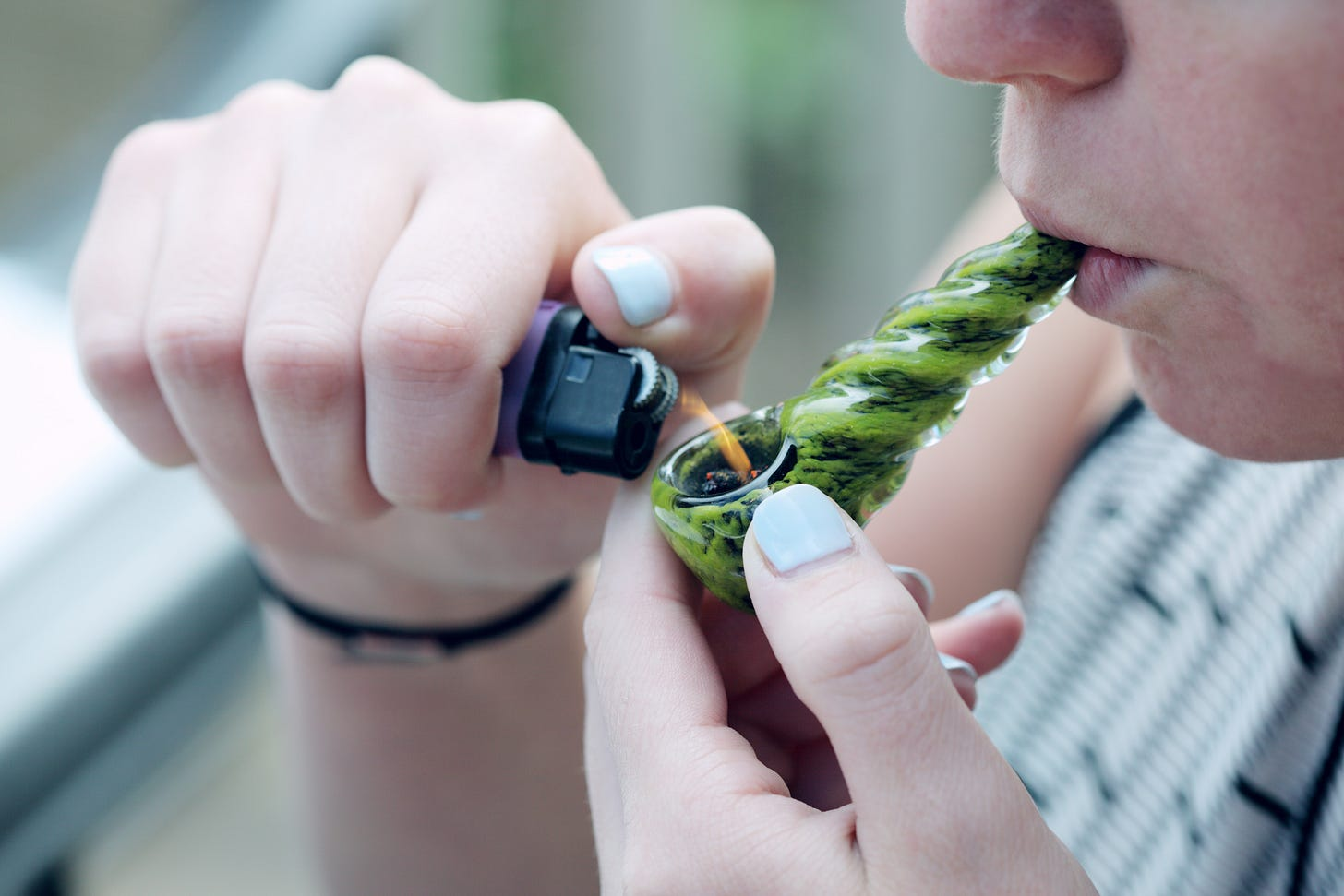 person with light blue nail polish lighting the bowl of a green glass pipe with marijuana in it