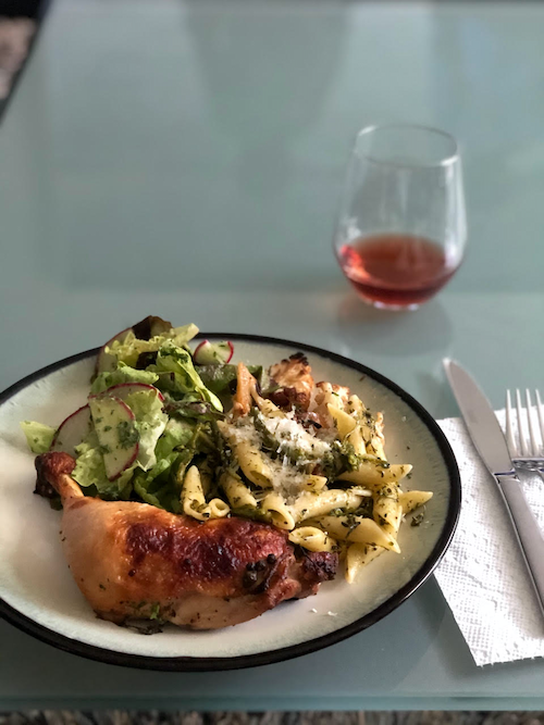 A dinner plate with roast chicken, salad, and pasta nest to silverware and a glass of red wine.