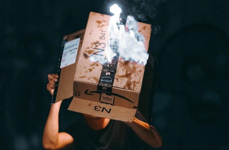 A man lights a cardboard Amazon box on fire.